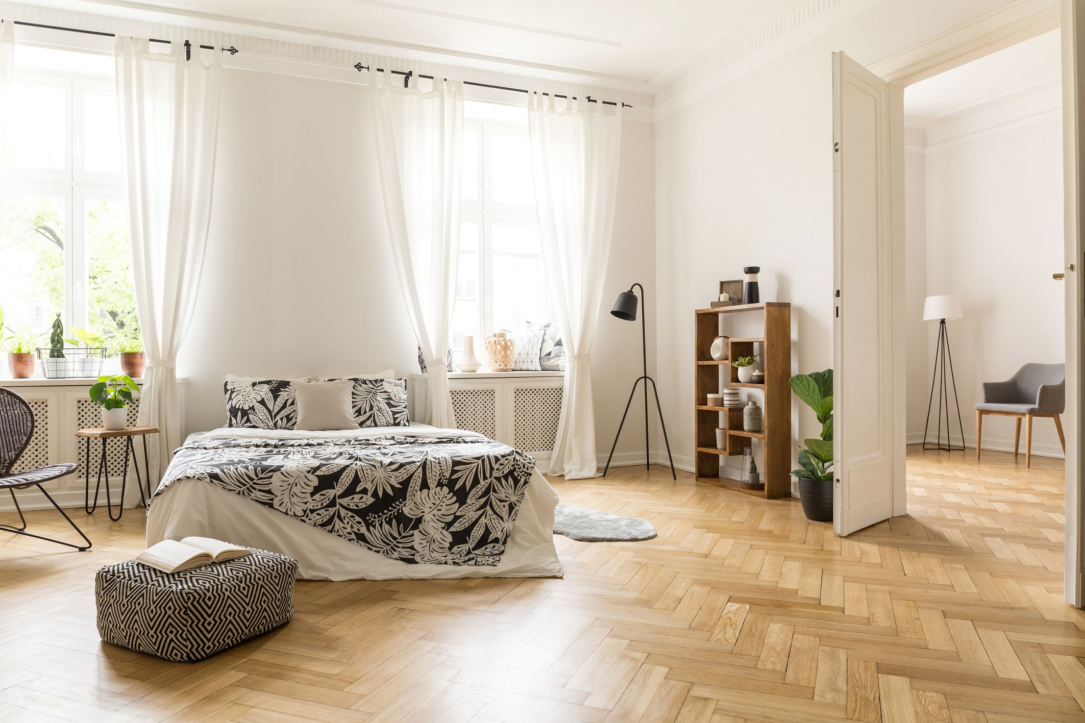 View at two rooms with white walls and herringbone parquet. A bed, a pouf, lamp bookcase and armchair in a natural style apartment interior. Real photo.