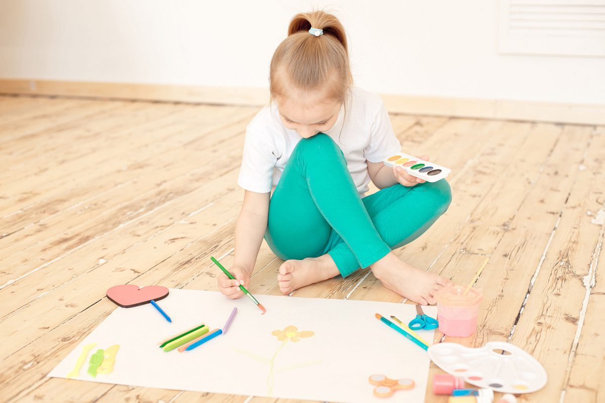 Little blonde girl paints on big white paper sitting on the floor indoors.