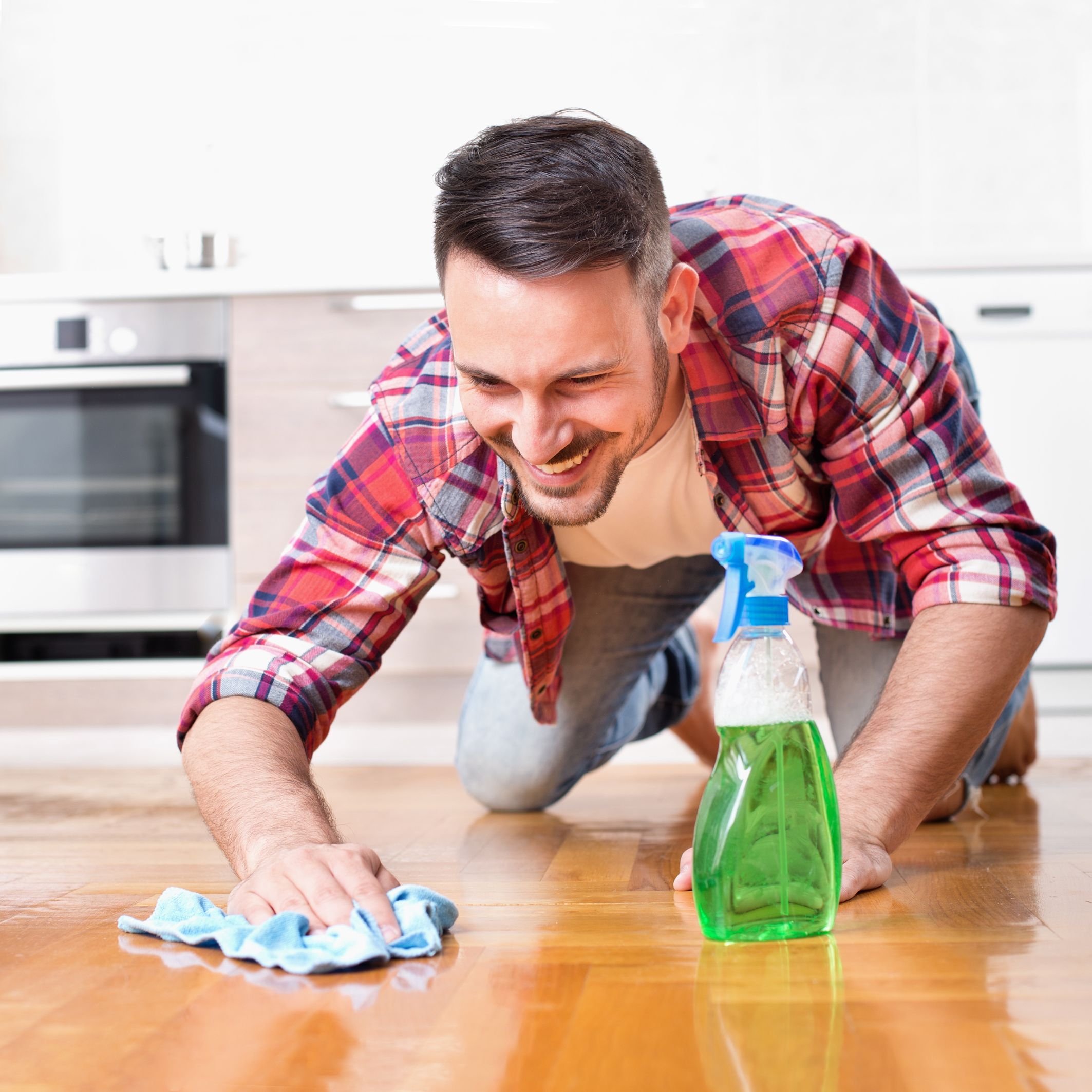 Happy handsome man wiping parquet floor. Husband housekeeping and cleaning concept. Home interior and kitchen in background
